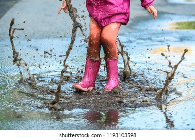 Playful child outdoor jump into puddle in boot after rain