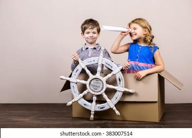 Playful childhood. Little children having fun with cardboard box. Children pretending to be on ship