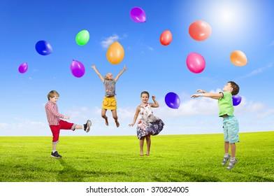 Playful children catch balloons
