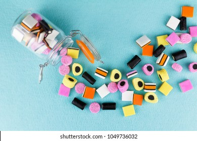 playful, colorful pile of candy liquorice allsorts spilling from jar top view