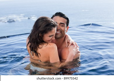 Playful couple cuddling each other in a swimming pool
