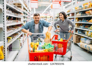 Playful couple ride on carts in supermarket
