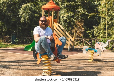 Playful crazy man (dad) riding wooden rocking horse in a park - adult guy (hipster with beard) having fun on a playground