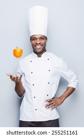 Playful culinary master. Confident young African chef in white uniform throwing pepper and looking at camera with smile while standing against grey background