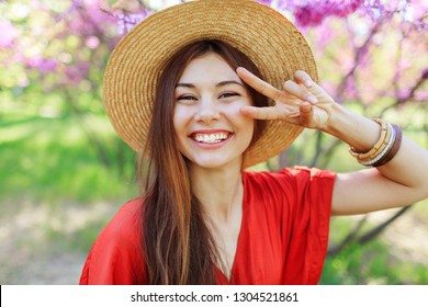 Playful cute girl making funny face and showing signs , posing in spring park on blooming trees background.