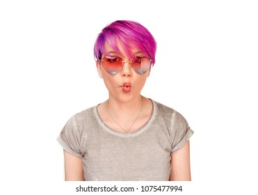 "Playful cute girl. Woman making a funny face known as a""fish-face"" puckering lips wearing heart shape pink sunglasses and trendy magenta hair style isolated on white wall background in studio shot."