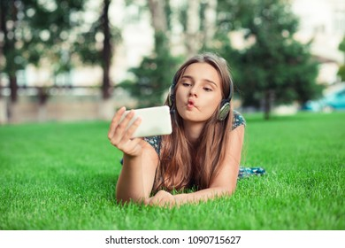 """Playful cute girl. Woman making a funny face known as a""""fish-face"""" puckering lips looking at phone lying down on green lawn trees on background with copy space. Multicultural model, asian russian girl"""