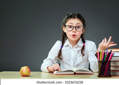 Playful cute little girl having fun while leaning on thick books on the grey background. Her hair is done in plaits. Tasty yellow and red apple is on the top of the book pile.