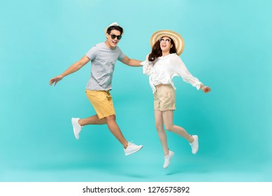 Playful energetic Asian couple in summer beach casual clothes jumping isolated on light blue background studio shot