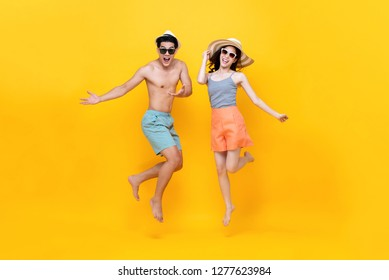 Playful energetic Asian couple in summer beach casual clothes jumping on yellow background studio shot