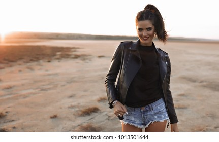 Playful excited fashion model with red lipstick, open mouth, gesturing and shoving her style. She is in a black jacket on the bright yellow background,over sunset sky,leather jacket,rock n roll,denim