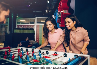 Playful excited young women playing table soccer with guy in room. Models loook at game and control it.