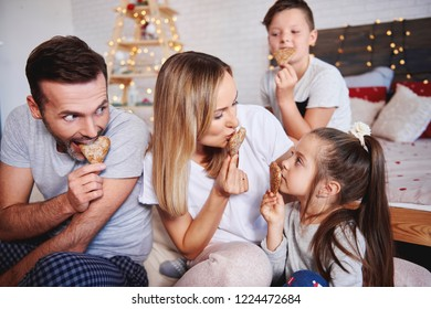 Playful family eating gingerbread cookies in bed