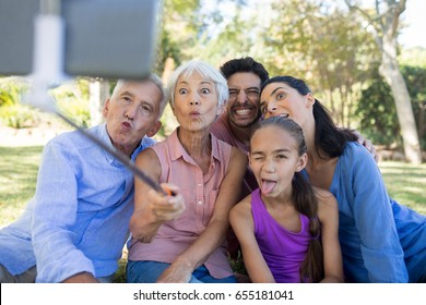 Playful family making funny faces while taking a selfie in the park