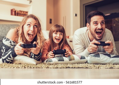 Playful family playing video games together in a living room.