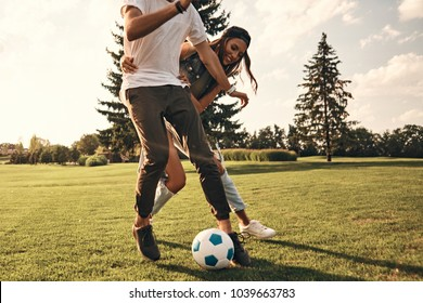 Playful friends. Group of young people in casual wear running while playing soccer outdoors
