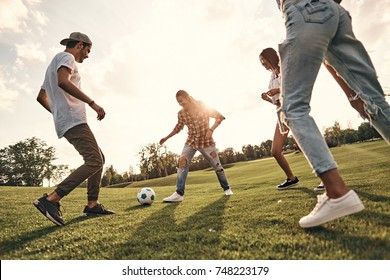 Playful friends. Group of young smiling people in casual wear playing soccer while standing outdoors