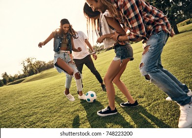 Playful friends. Group of young smiling people in casual wear enjoying nice summer day while playing soccer outdoors