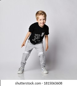Playful frolic blond kid boy in sunglasses, black t-shirt with dinosaur print and gray pants stands leaning forwards going to run out playing catch-up over gray background
