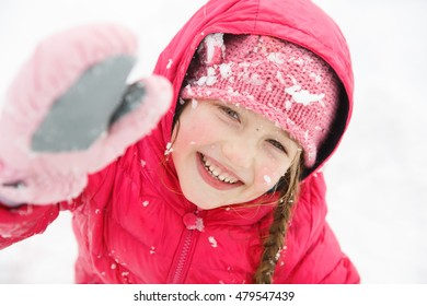 Playful girl with braids, enjoying winter and snow, dressed in warm clothes, playing and catching some sun. Active family lifestyle, outdoor and natural childhood, carefree childhood concept.