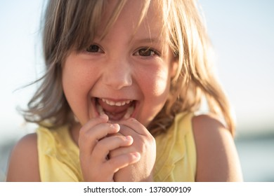 Playful girl child wearing a bright smile, closeup shot.