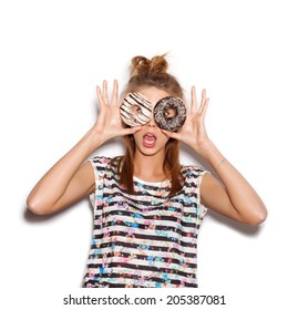 Playful girl holding donuts on her eyes. Woman showing own. White background, not isolated