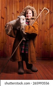 Playful girl shepherd with his staff under his arm a lamb on the farm
