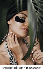 Playful girl in turban touching palm tree leaf. Outdoor shot of joyful lady with eye patches.