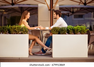 Playful girlfriend is flirting with guy by her leg, lovers are sitting in light cafe on a sunny day and enjoy coffee with tasies, talking, smiling, looking at each other