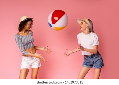 Playful girls in summer wear playing with big beach ball, pink studio background