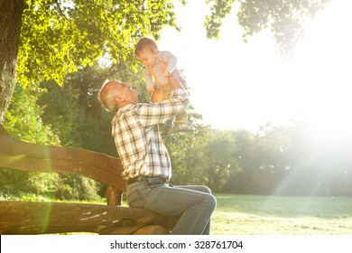 Playful grandfather spending time with his grandson in park on sunny day