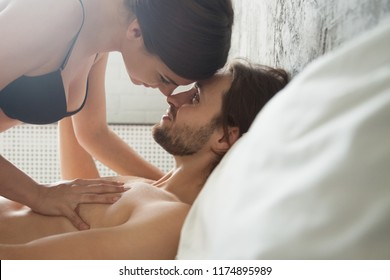 Playful half naked girlfriend caress loving boyfriend in bed, couple enjoy prelude before sex or love making, passionate lovers face to face look at each other having foreplay intimacy in bedroom