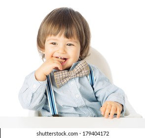 Playful happy baby boy holding hands in the mouth, Child Model with romantic Fashion outfit suspenders and tie bow, delighted and smiling. Studio shot, isolated, over white background with copy space