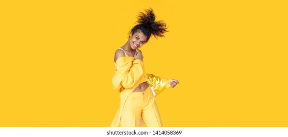 Playful happy young african woman wear stylish yellow clothes look at camera dancing funky black teen fashion girl on summer studio background, horizontal banner header website design, copy space