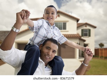 Playful Hispanic Father and Son in Front of Beautiful House.