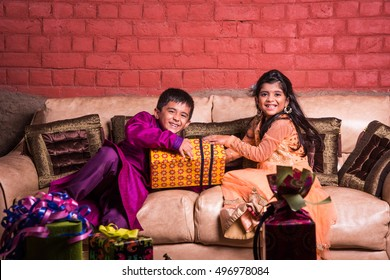 Playful Indian/Asian kids in ethnic wear with Diwali gifts, smiling or fighting for gifts while sitting on Sofa