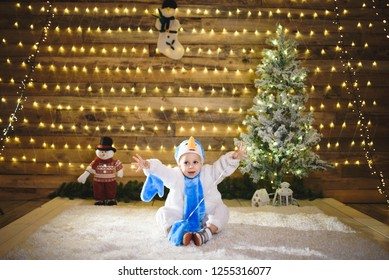 playful kid in snowman suit at christmas tree