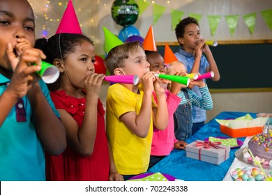 Playful kids blowing party horns while standing by table