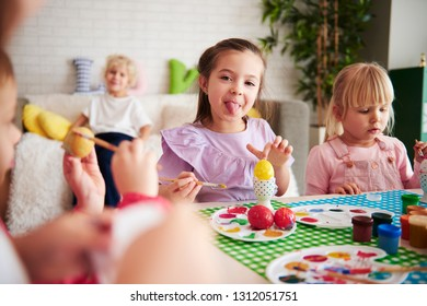 Playful kids decorating easter eggs