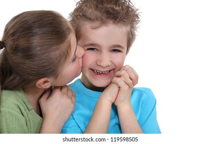 Playful little boy being kissed by a little girl