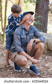 Playful little boy covering fathers eyes while hiking in forest