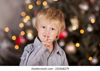 Playful little boy keeping a Christmas secret standing in front of the tree making a shushing gesture with his finger to his lips