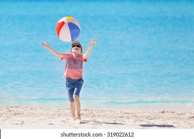 playful little boy playing with beach ball at the caribbean beach