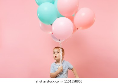 Playful little cute child baby boy holding bunch of colorful air balloons, celebrating birthday holiday party on pastel color pink background. Family day kids children childhood lifestyle concept