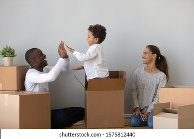 Playful little cute mixed race preschool boy jumping out of big cardboard box, giving high five to smiling african american young dad. Happy millennial woman watching husband playing with small son.