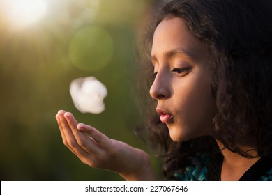 playful little girl blowing the cotton ball, outdoor portrait of cute Indian girl.