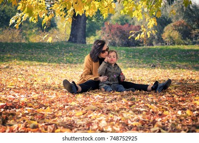Playful little girl and her mother blowing soap bubbles. Mother and daughter having fun with bubble wand while relaxing in autumn leaves.