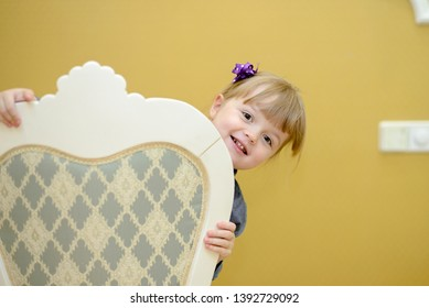 Playful little girl peeking out from behind a chair