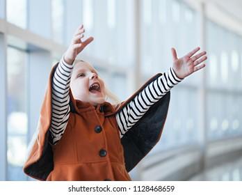 Playful little girl wearing orange coat shouting with joy