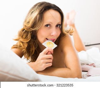 Playful long-haired adult woman holding condom in bed
